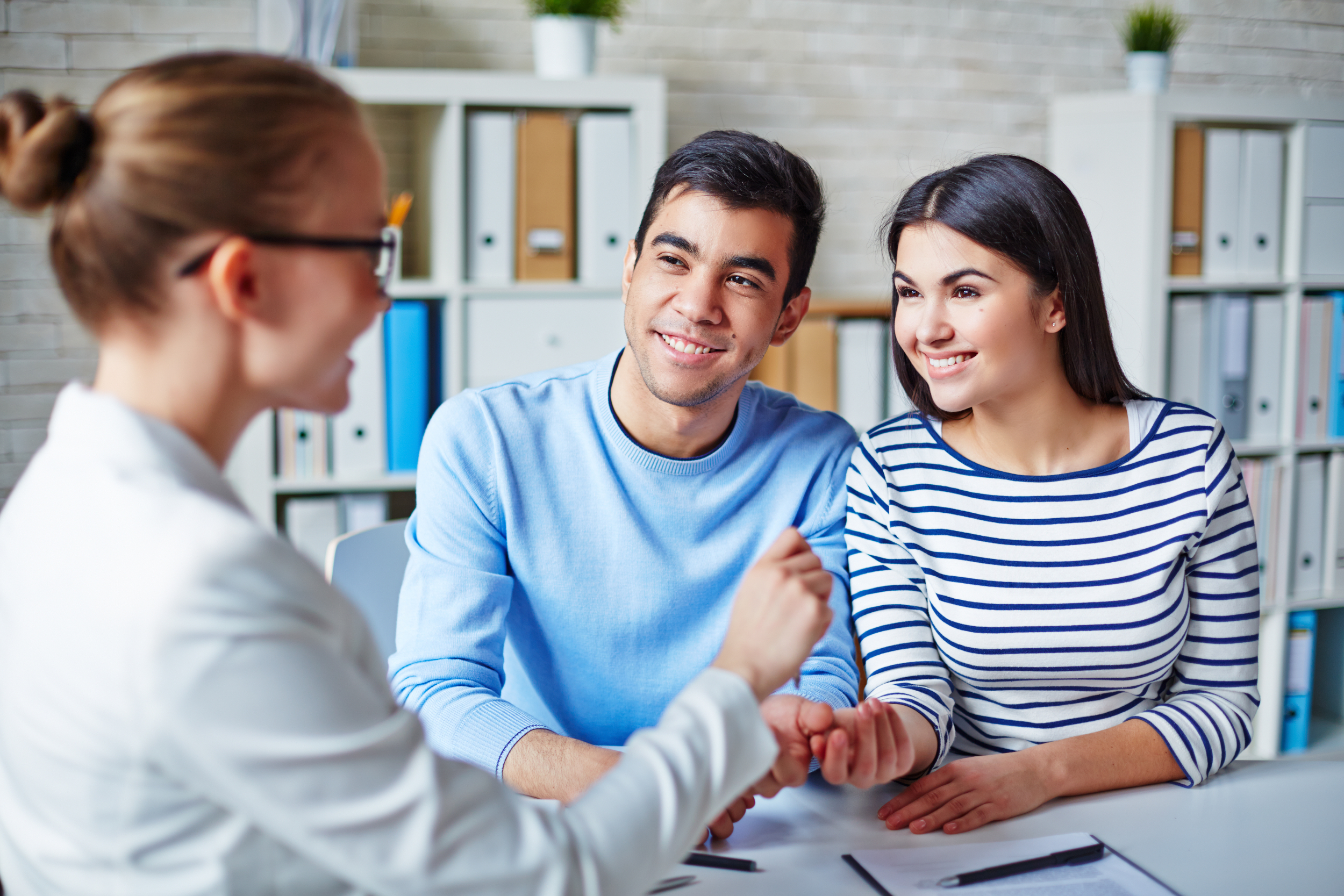 A young couple meeting with an agent to buy a home